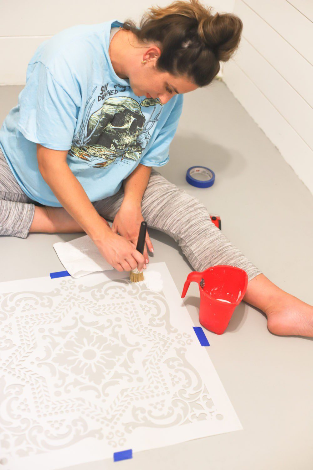 Laundry Room DIY: How to Paint a Cement Floor with Stencils | Laundry Room DIY: How to Paint a Cement Floor with Stencils by popular home decor blog, Fresh Mommy: image of a woman painting her cement floor.
