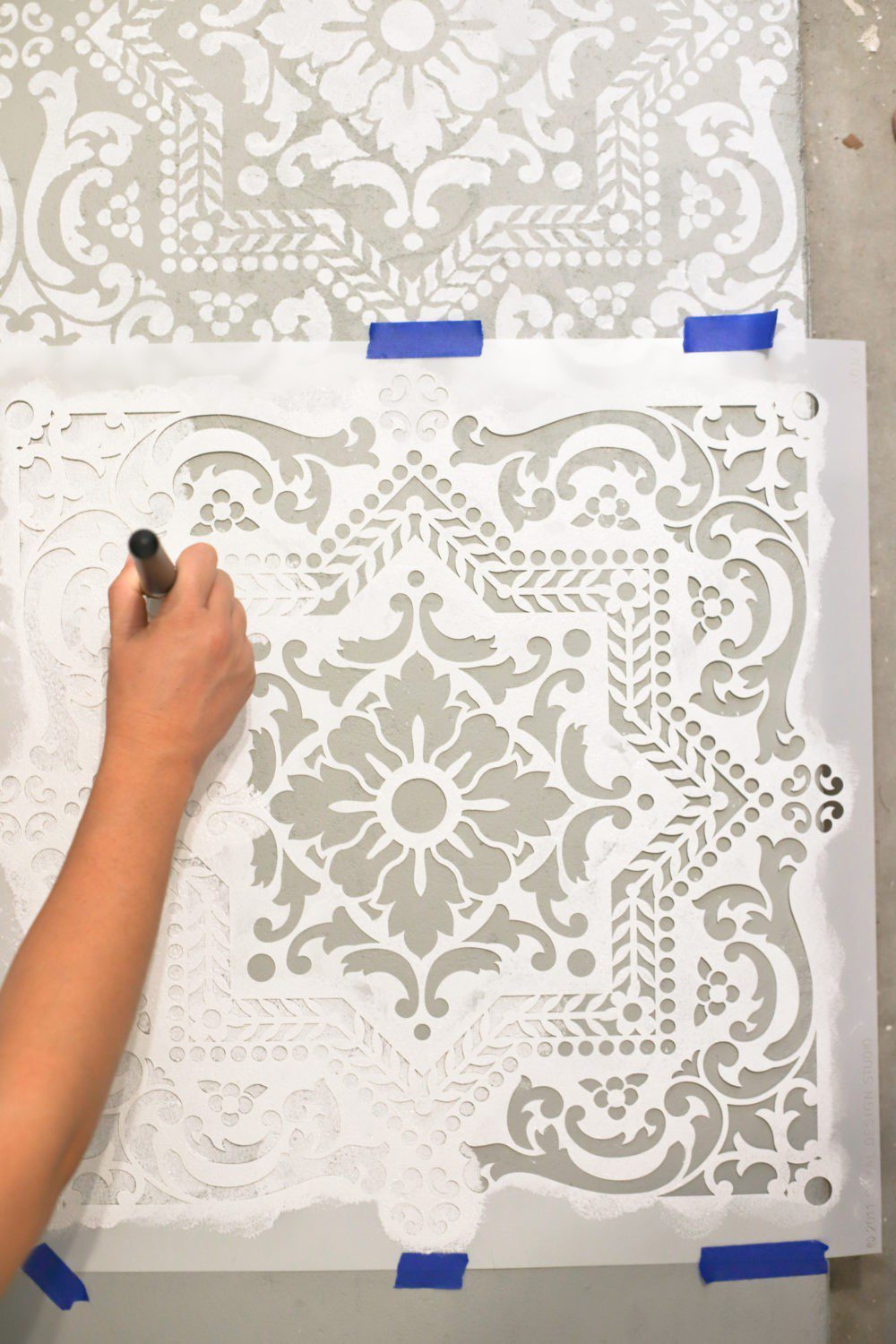 Laundry Room DIY: How to Paint a Cement Floor with Stencils | Laundry Room DIY: How to Paint a Cement Floor with Stencils by popular home decor blog, Fresh Mommy: image of a cement floor being painted with a stencil and white floor paint.