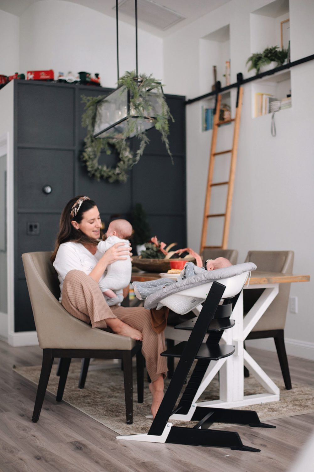 Tutorial: DIY Wood Grid Wall | Tutorial: Board and Batten Grid Wall by popular Florida DIY blog, Fresh Mommy Blog: image of a woman sitting in a chair and holding her baby in front of a board and batten grid wall.