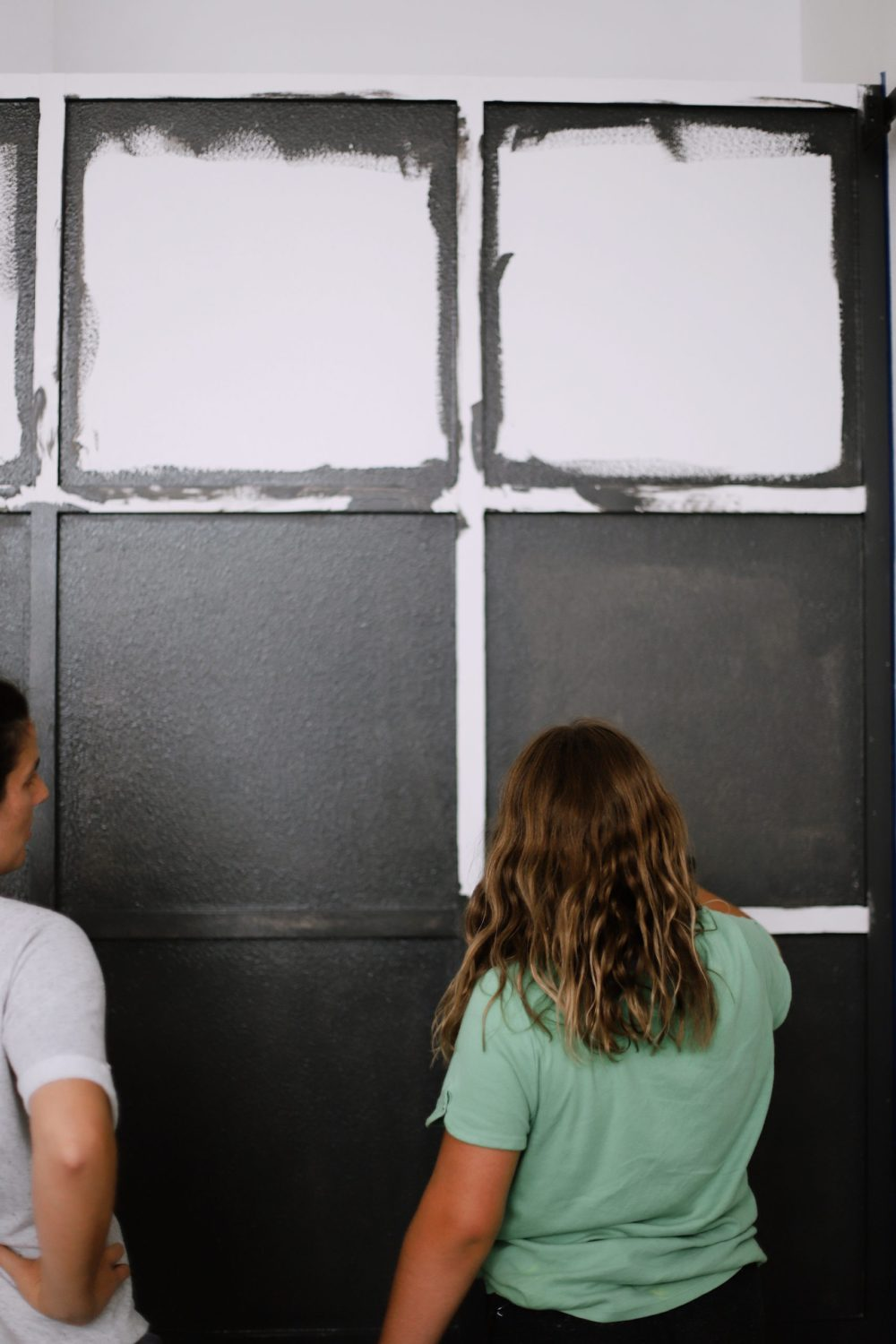 BEFORE AND AFTER Tutorial: DIY Wood Grid Wall! How to create a stunning and bold accent wall with a DIY wooden grid. Click for the full tutorial.   Tutorial: Board and Batten Grid Wall by popular Florida DIY blog, Fresh Mommy Blog: image of a woman applying black paint to a board and batten grid wall.