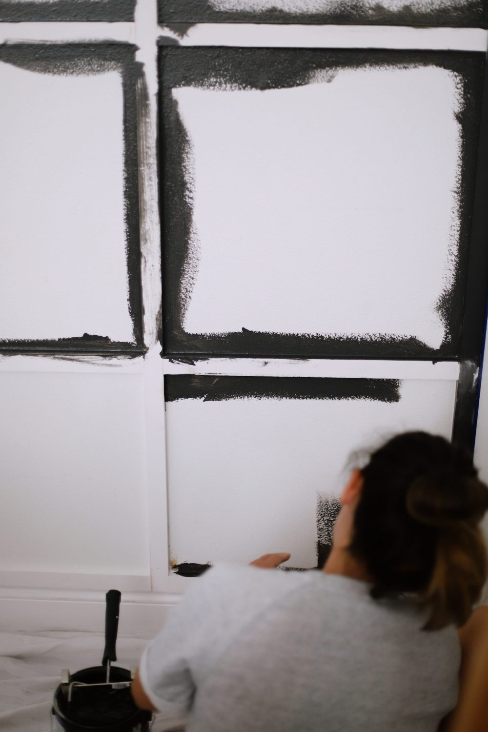 BEFORE AND AFTER Tutorial: DIY Wood Grid Wall! How to create a stunning and bold accent wall with a DIY wooden grid. Click for the full tutorial. | Tutorial: Board and Batten Grid Wall by popular Florida DIY blog, Fresh Mommy Blog: image of a woman applying black paint to a board and batten grid wall.