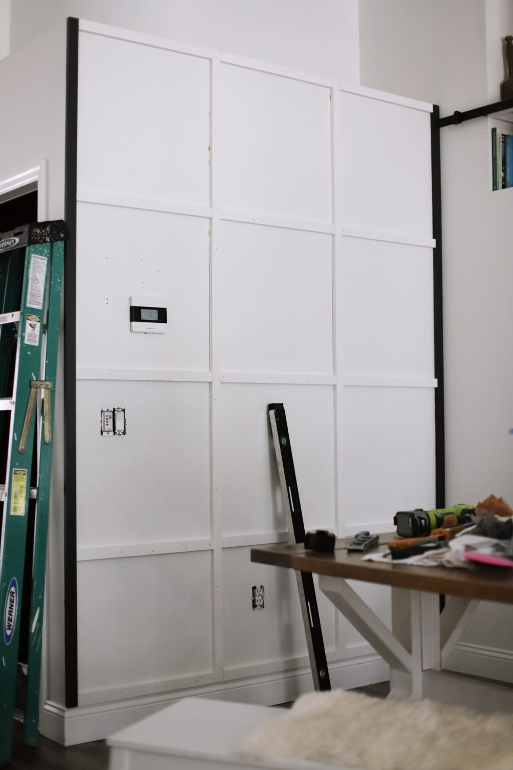 BEFORE AND AFTER Tutorial: DIY Wood Grid Wall! How to create a stunning and bold accent wall with a DIY wooden grid. Click for the full tutorial. | Tutorial: Board and Batten Grid Wall by popular Florida DIY blog, Fresh Mommy Blog: image of a white board and batten grid wall.