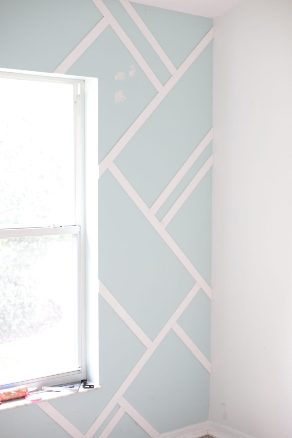 Gorgeous Wood Feature Wall + Shared Girl's Room Update by popular Florida home decor blog, Fresh Mommy Blog: before image of a man installing a wood accent wall in a shared girls' room.