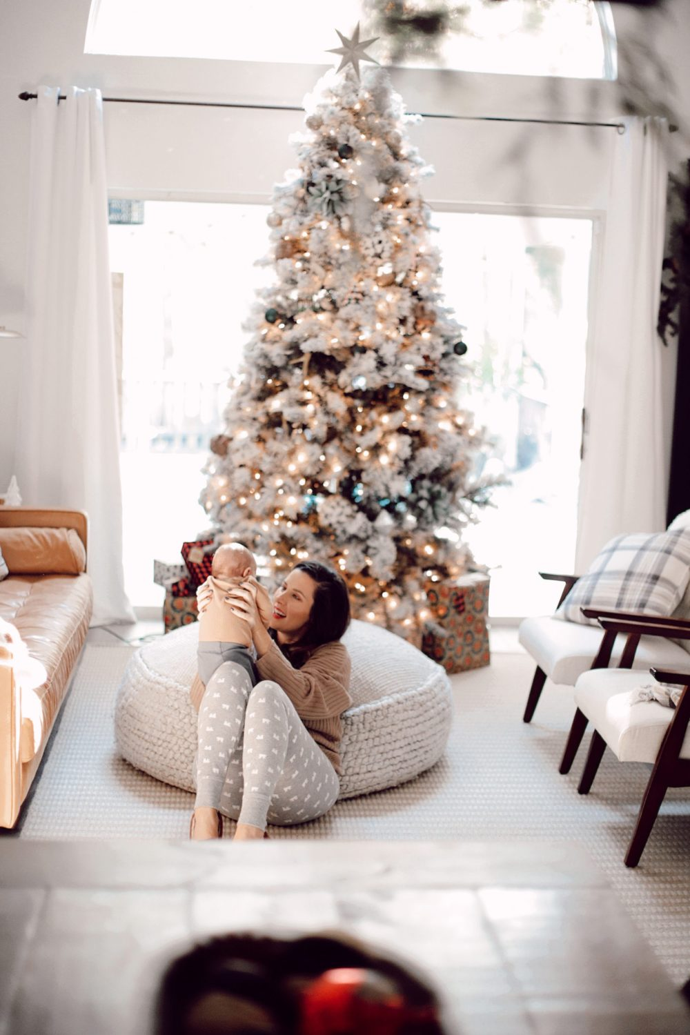 7 Geniously Efficient Mom Hacks for Home Design | 7 Genius Efficient Home Design Hacks for Moms by popular Florida life and style blog, Fresh Mommy Blog: image of a mom sitting on the floor in her living room and holding her new born baby.