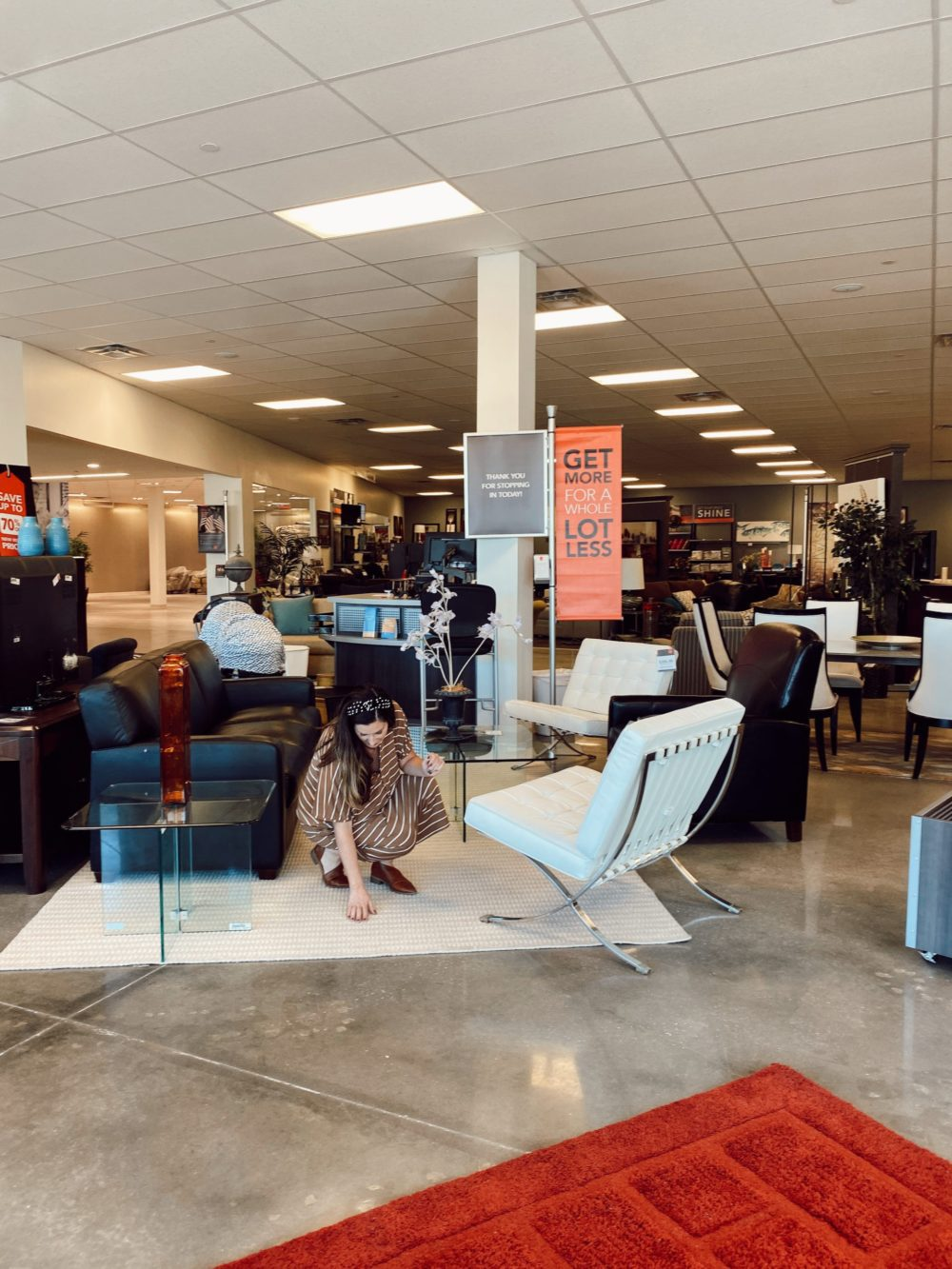 7 Geniously Efficient Mom Hacks for Home Design | 7 Genius Efficient Home Design Hacks for Moms by popular Florida life and style blog, Fresh Mommy Blog: image of a mom looking at a rug at CORT furniture outlet.