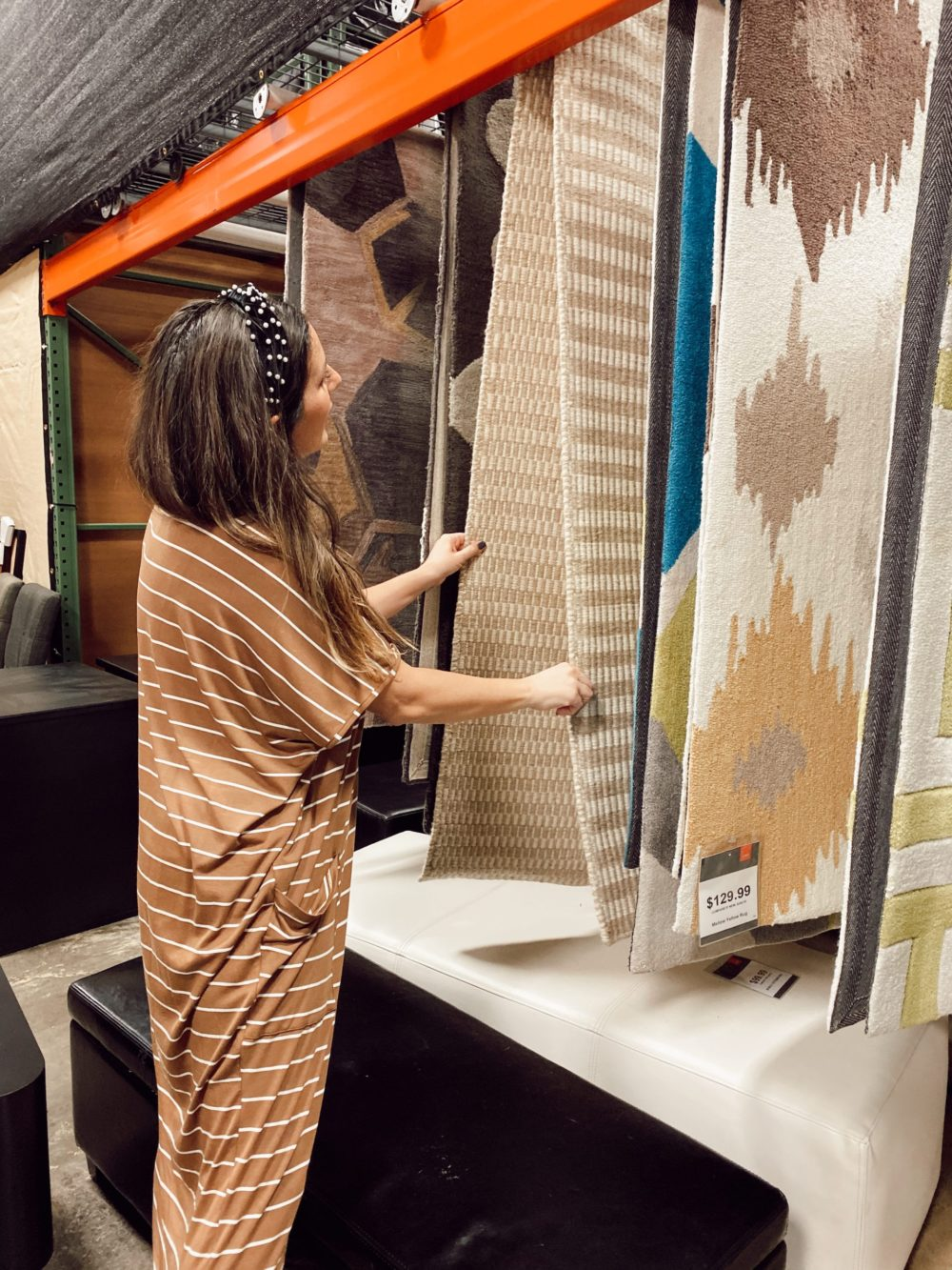7 Genius Efficient Home Design Hacks for Moms by popular Florida life and style blog, Fresh Mommy Blog: image of a mom looking at rugs at CORT Furniture Outlet.