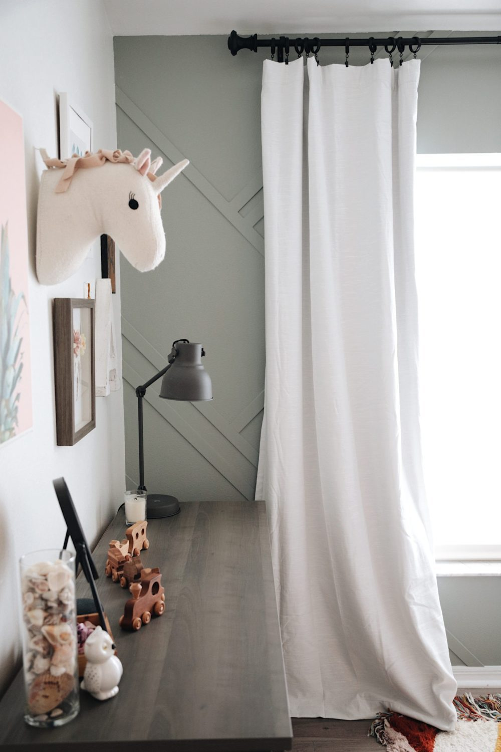 Shared girl's room design inspiration and how to DIY a gorgeous feature wall | Gorgeous Wood Feature Wall + Shared Girl's Room Update by popular Florida home decor blog, Fresh Mommy Blog: image of a shared girls' room decorated with a Lowe's South Shore Furniture Versa Gray Maple 6-Drawer Double Dresser, Lowe's LEVOLOR Trim+Go Shadow Light Filtering Cordless Solar Shade, Lowe's allen + roth 2-Pack Black Curtain Rod Finials, Lowe's Paint Paints & Primers Paint Samples Item # 1185292 Model # 5005-2A Valspar Secret Moss Interior Paint, Lowe's DAP DryDex 8-oz White Spackling, Lowe's allen + roth Matte Black 72-in To 144-in Matte Black Steel Single Curtain Rod, and Lowe's allen + roth LL WARWICK 42-IN x 84-IN TAUP PNL 84-in Taupe Polyester Blackout Thermal Lined Single Curtain Panel.