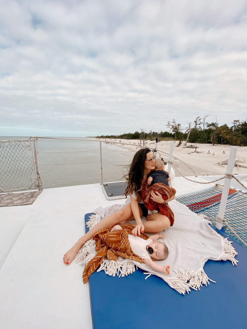 Relaxing catamaran trip with Sweet Liberty, the largest Sailing Catamaran in Southwest Florida. Baby-friendly activity in Florida! | Spectacular Things to Do in Naples FL This Weekend by popular Florida blog, Fresh Mommy Blog: image of a woman sitting on a boat with her twin babies.
