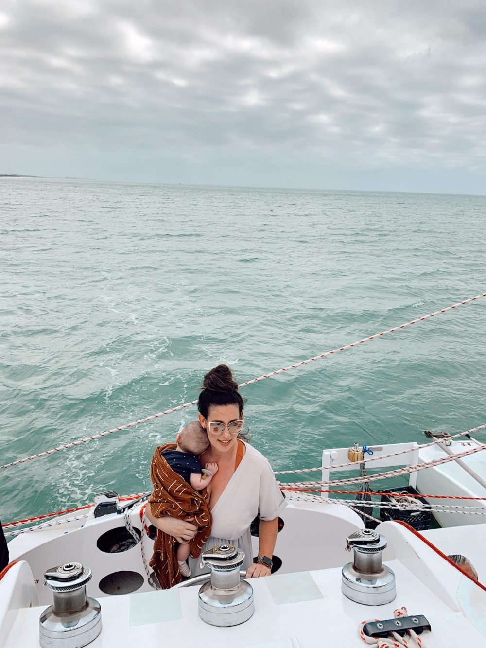 Relaxing catamaran trip with Sweet Liberty, the largest Sailing Catamaran in Southwest Florida. Baby-friendly and we got to steer the boat! | Spectacular Things to Do in Naples FL This Weekend by popular Florida blog, Fresh Mommy Blog: image of a woman holding a baby on a sailboat.