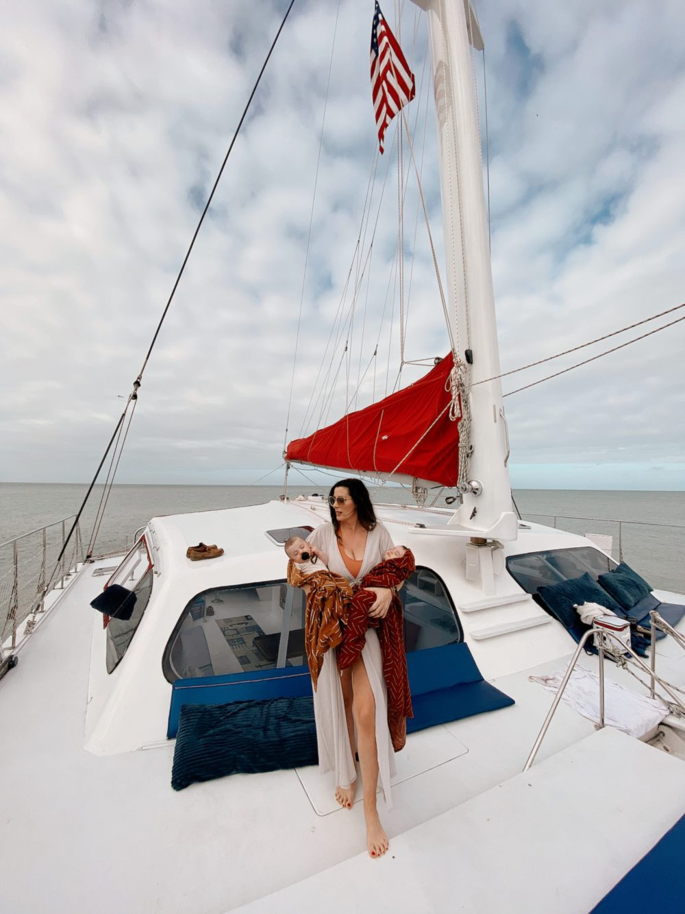 Relaxing catamaran trip with Sweet Liberty, the largest Sailing Catamaran in Southwest Florida... babies welcome! | Spectacular Things to Do in Naples FL This Weekend by popular Florida blog, Fresh Mommy Blog: image of a woman standing on a boat with her twin babies.