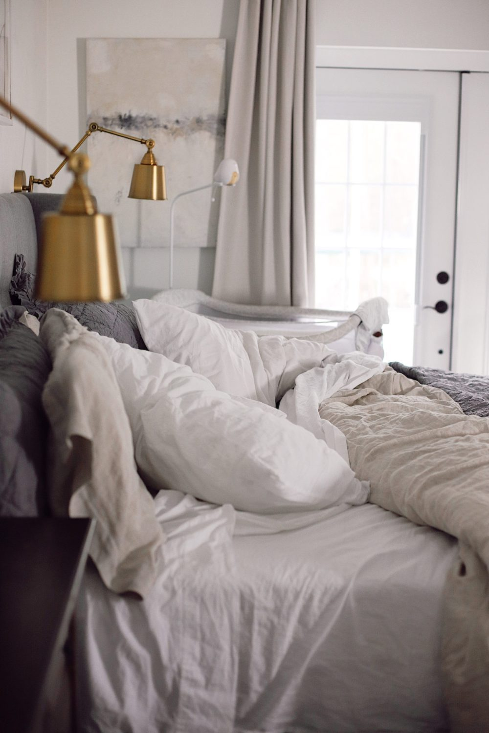 7 Steps to Create a Cozy, Dream Bed You Won't Want to Leave | Best Baby Monitor by popular Florida motherhood blog, Fresh Mommy Blog: image of a unmade bed next to a bassinet.