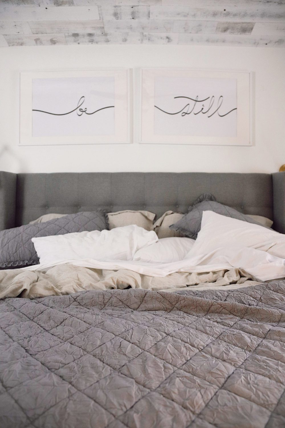 how to Make your Bed Comfortable Like a Hotel in 7 Easy Steps, a tutorial featured by top Florida lifestyle blog, Fresh Mommy Blog. | Best Bedding by popular Florida life and style blog, Fresh Mommy: image of a unmade bed with the words 'Be Still' hanging above it.
