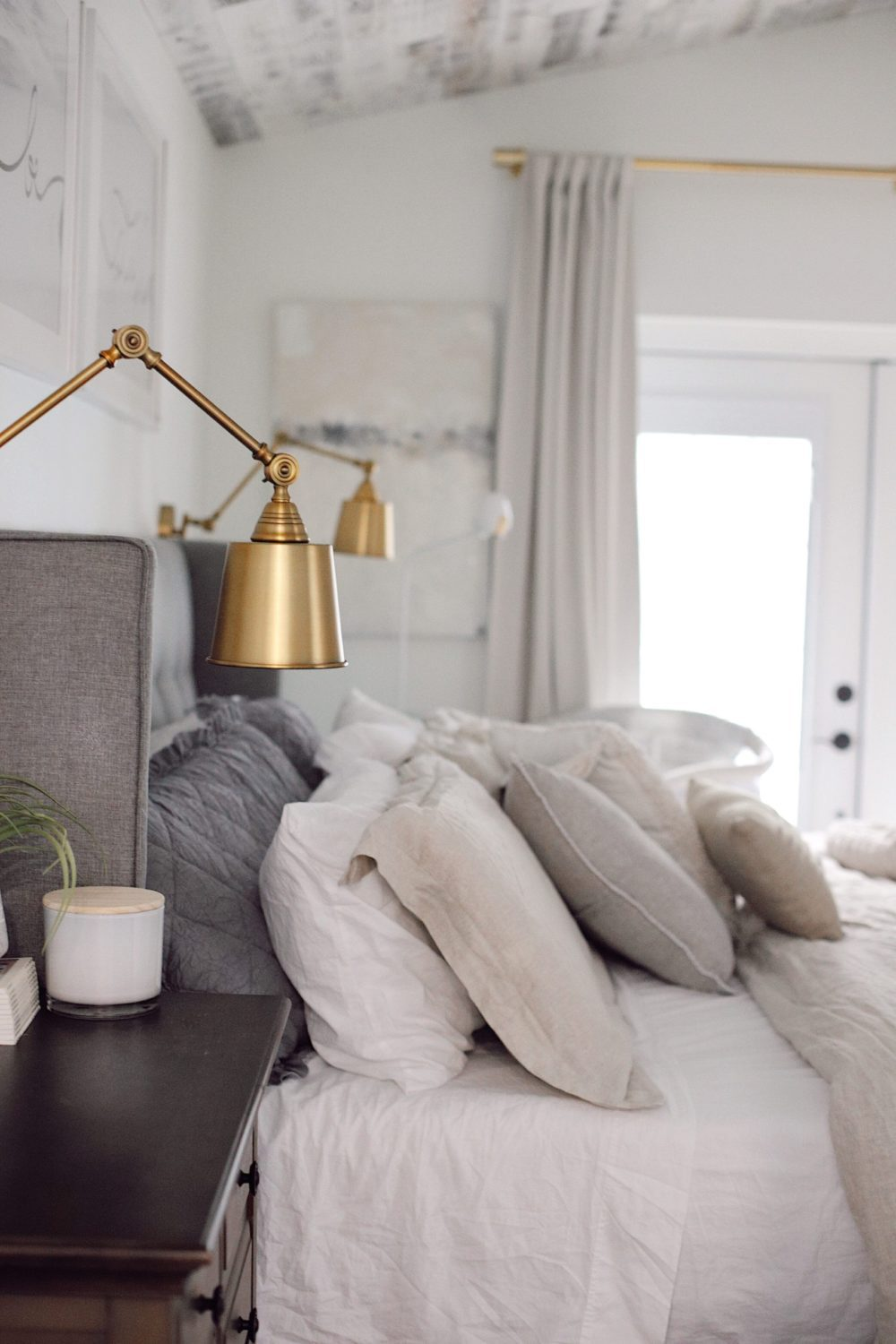 how to Make your Bed Comfortable Like a Hotel in 7 Easy Steps, a tutorial featured by top Florida lifestyle blog, Fresh Mommy Blog. | Best Bedding by popular Florida life and style blog, Fresh Mommy: image of a comfortable bed with an upholstered head board and brass sconces.