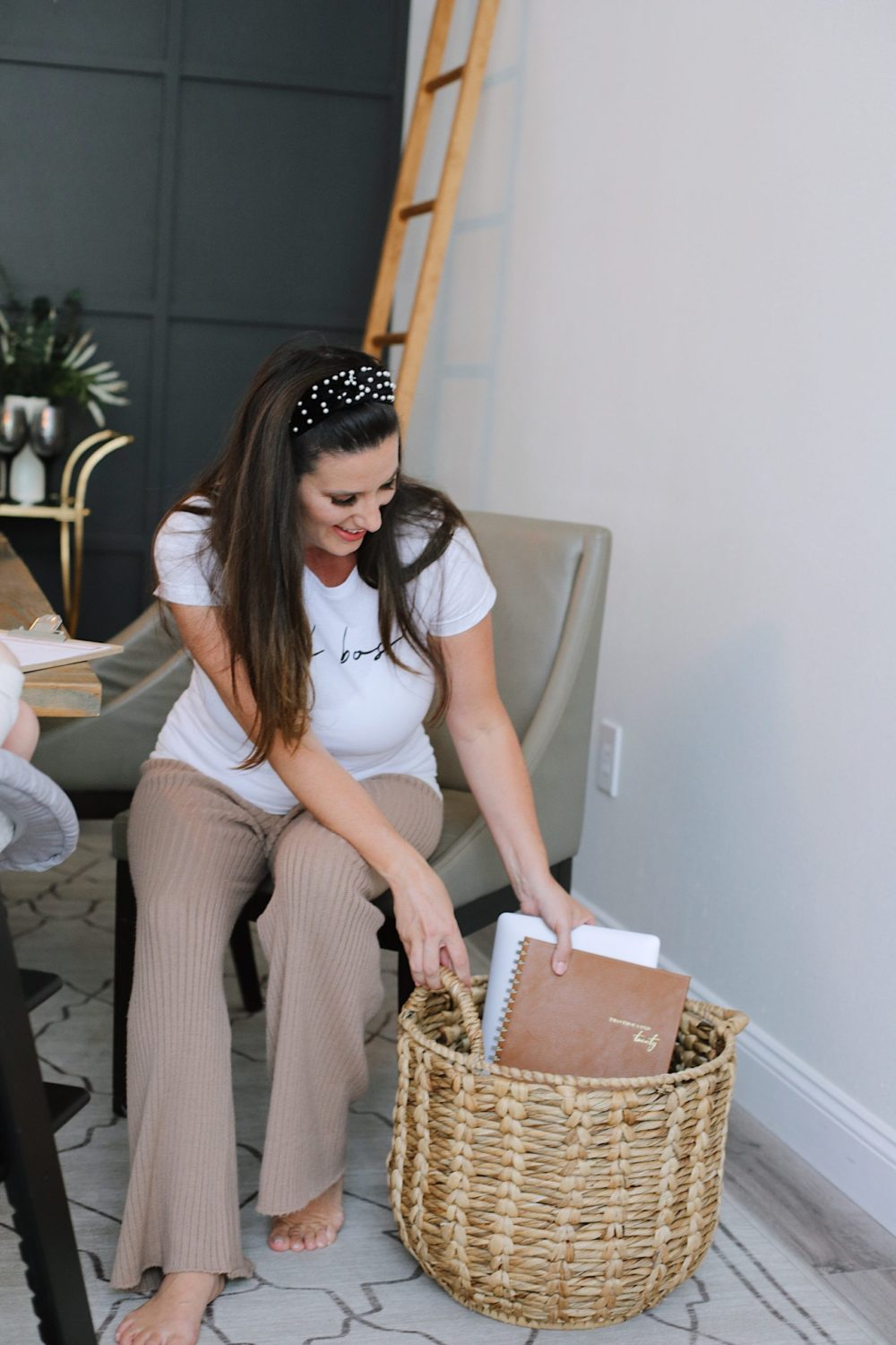How to Survive Working With Kids at Home - Tips for making the most of working from home with kids homeschooling. Click through for tips from lifestyle blogger Tabitha Blue of Fresh Mommy Blog! | Working From Home With Kids by popular Florida lifestyle blog, Fresh Mommy Blog: image of a mom placing a laptop and a planner in a wicker basket.