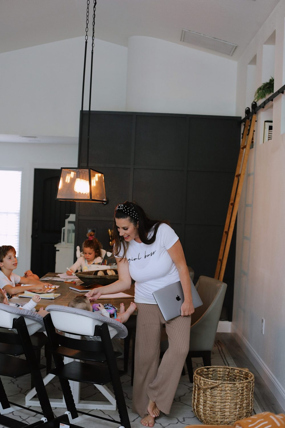 How to Survive Working With Kids at Home - Tips for making the most of working from home with kids homeschooling. Click through for tips from lifestyle blogger Tabitha Blue of Fresh Mommy Blog! | Working From Home With Kids by popular Florida lifestyle blog, Fresh Mommy Blog: image of a mom standing at a table with her kids while they do their homeschooling work.