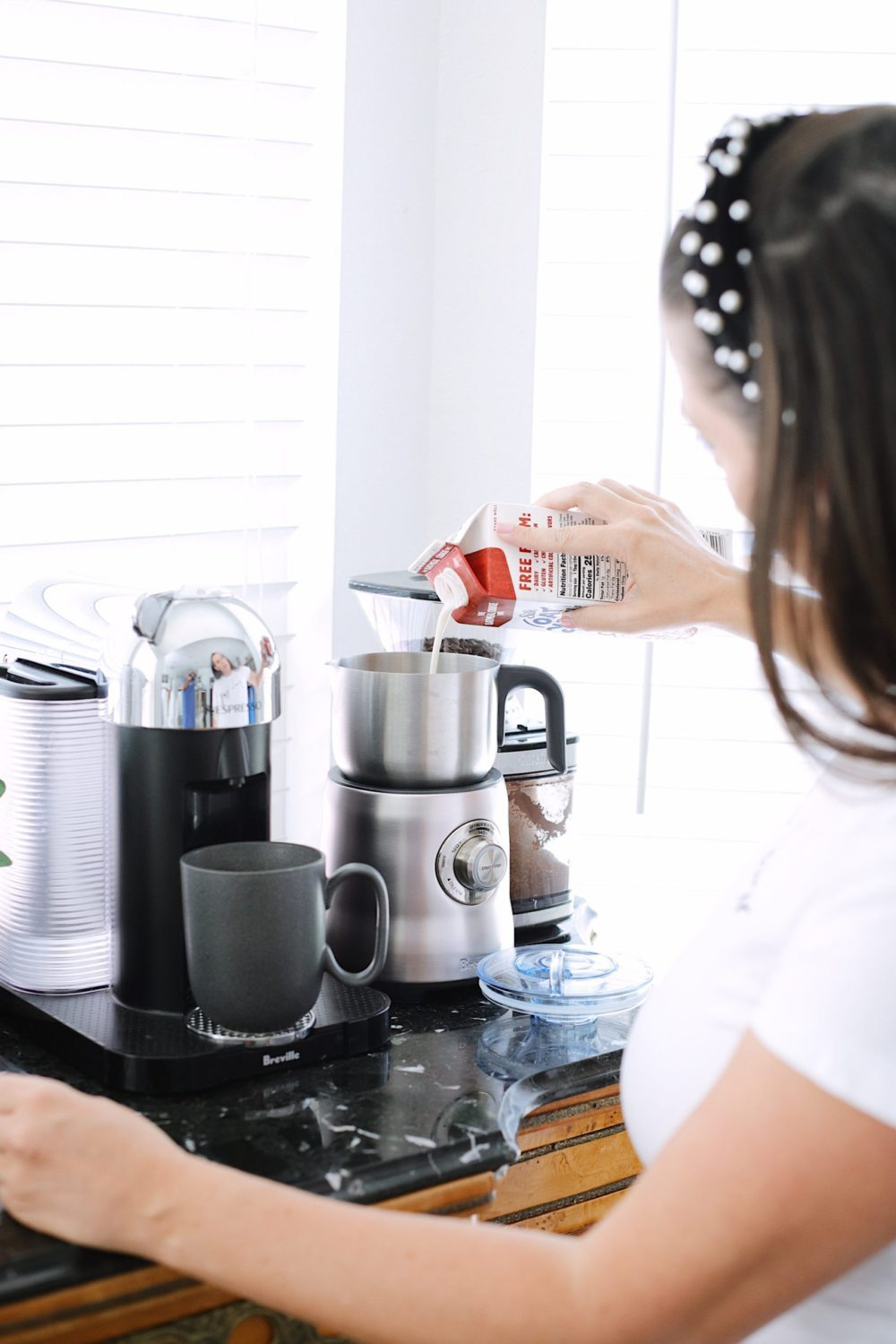 How to Survive Working With Kids at Home - Create your favorite coffee shop copy cat latte recipe in your own kitchen while working from home. | Working From Home With Kids by popular Florida lifestyle blog, Fresh Mommy Blog: image of a woman using a her Breville coffee milk frother.