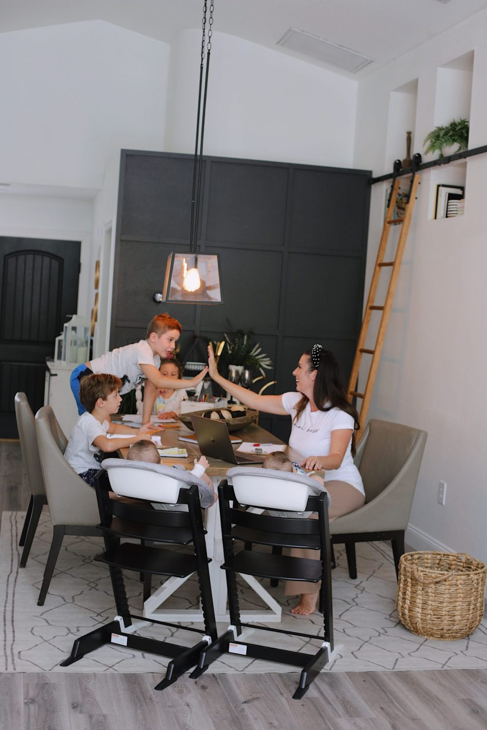 How to Survive Working With Kids at Home | Working From Home With Kids by popular Florida lifestyle blog, Fresh Mommy Blog: image of a mom sitting at a table with her kids while they do their homeschooling work.