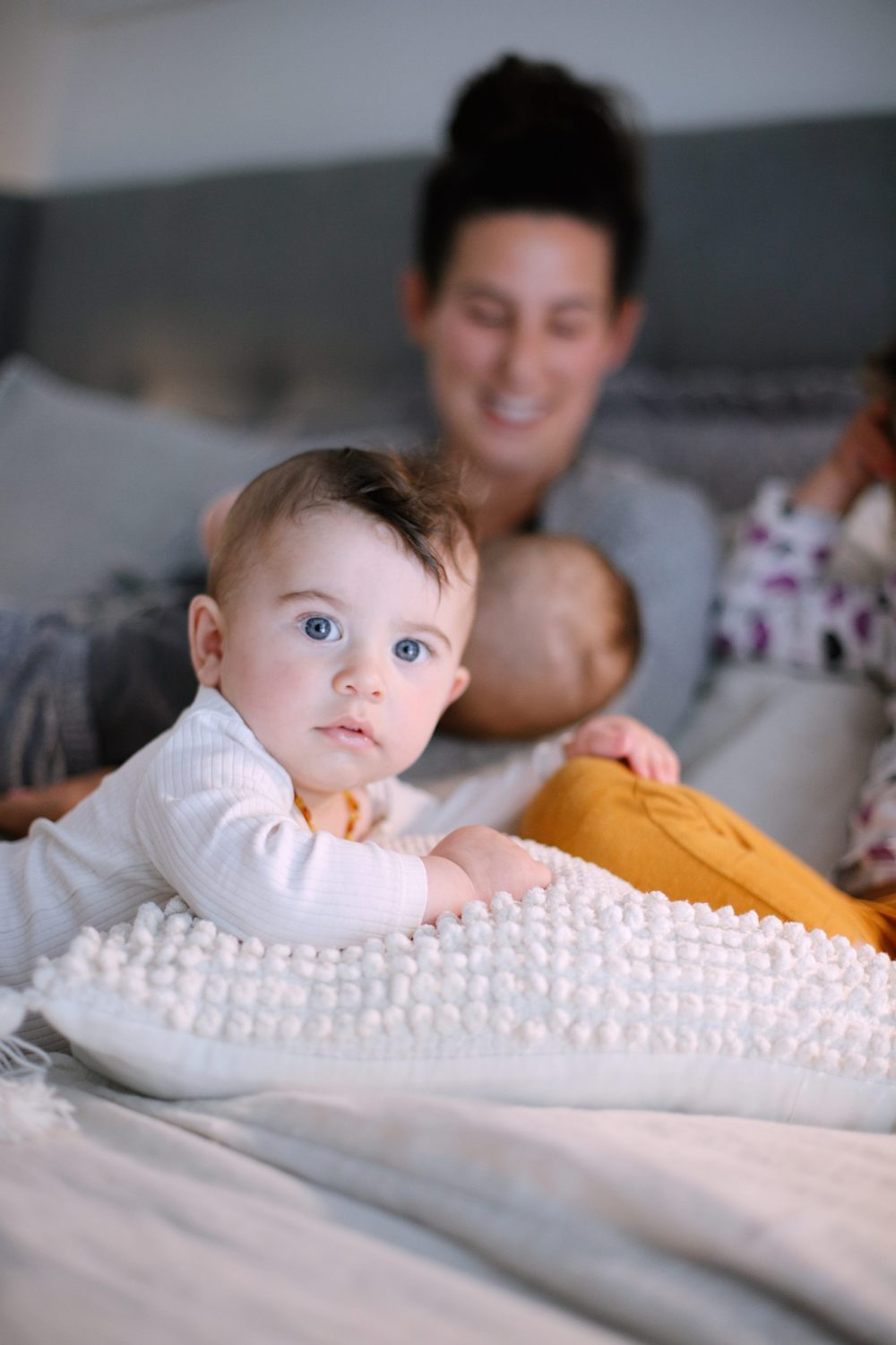 Best Baby Monitor by popular Florida motherhood blog, Fresh Mommy Blog: image of a mom holding her twin babies while sitting on a bed.