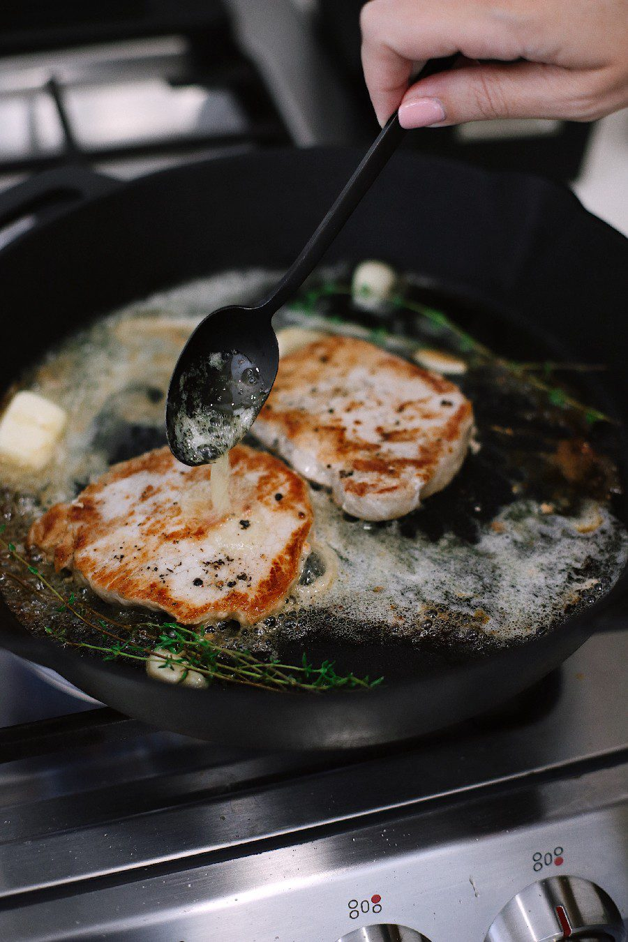 How To Cook Tender Skillet Pork Chops in the Oven What if I told you we figured out how to make sure to get those tender, juicy skillet pork chops every time, with a quick roast in the oven? Ready to say goodbye to dry, flavorless chops? These tips will have you adding tender pork chops back to your rotation. Try our pork chop recipe with browned butter garlic sauce! | Skillet Pork Chops by popular Florida lifestyle blog, Fresh Mommy Blog: image of a woman cooking skillet pork chops in her kitchen.