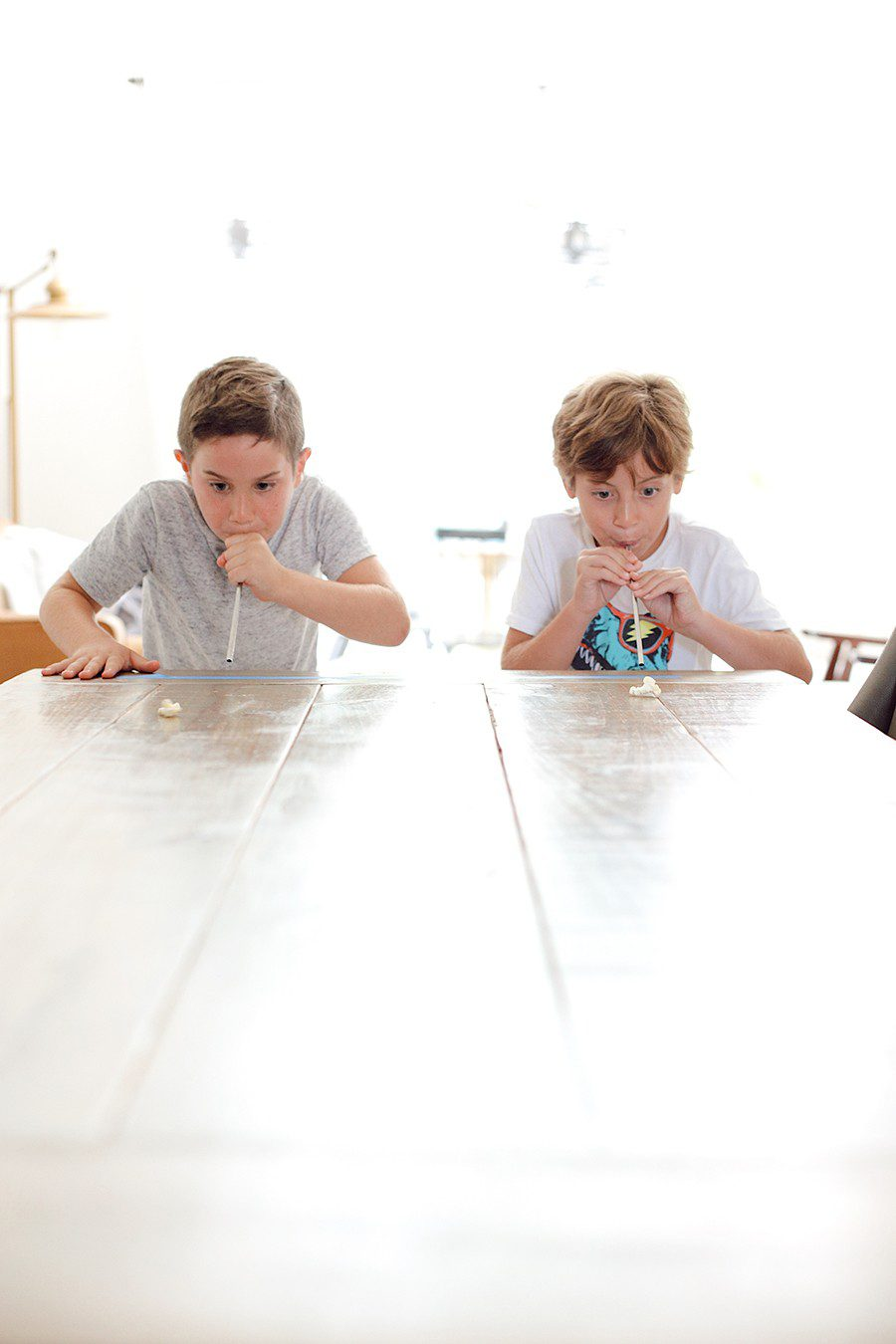 Popcorn race and more fun popcorn games for family game night! | Family Fun Night by popular Florida lifestyle blog, Fresh Mommy Blog: image of some kids blowing a piece of popcorn across a table with some straws.