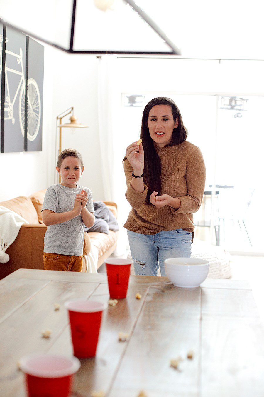 Popcorn toss and more fun popcorn games for family game night! | Family Fun Night by popular Florida lifestyle blog, Fresh Mommy Blog: image of Tabitha Blue tossing popcorn into red plastic cups.