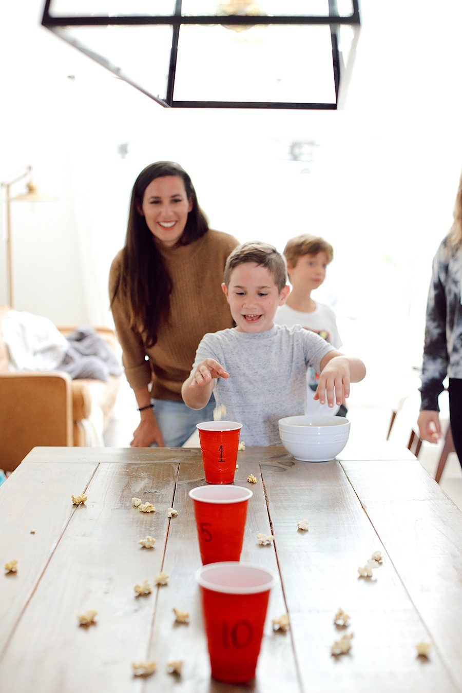 10 Popcorn Games for a Great Family Fun Night | Family Fun Night by popular Florida lifestyle blog, Fresh Mommy Blog: image of a mom and her kids tossing popcorn into red plastic cups.