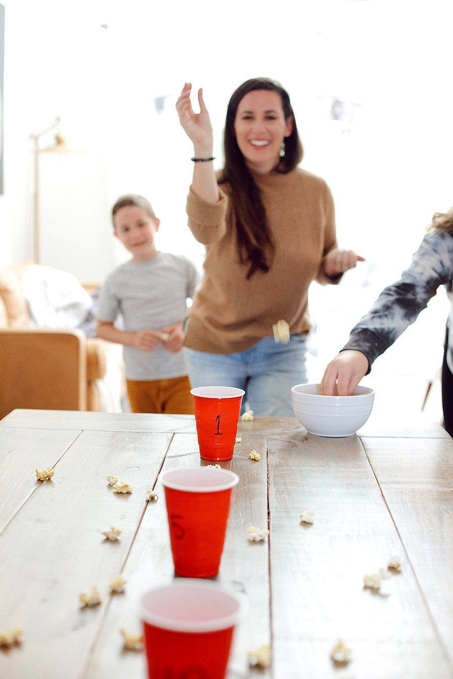 10 Popcorn Games for a Great Family Fun Night | Family Fun Night by popular Florida lifestyle blog, Fresh Mommy Blog: image of Tabitha Blue tossing popcorn into red plastic cups.
