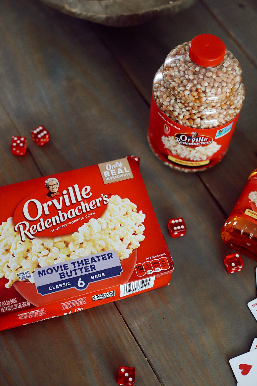10 Popcorn Games for a Great Family Fun Night | Family Fun Night by popular Florida lifestyle blog, Fresh Mommy Blog: image of bowl full of popped Orville Redenbacher's popcorn, a box of Orville Redenbacher's movie theater butter microwave popcorn, a deck of face cards, red dice, red plastic cups, and a plastic bottle of Orville Redenbacher's popcorn kernels.