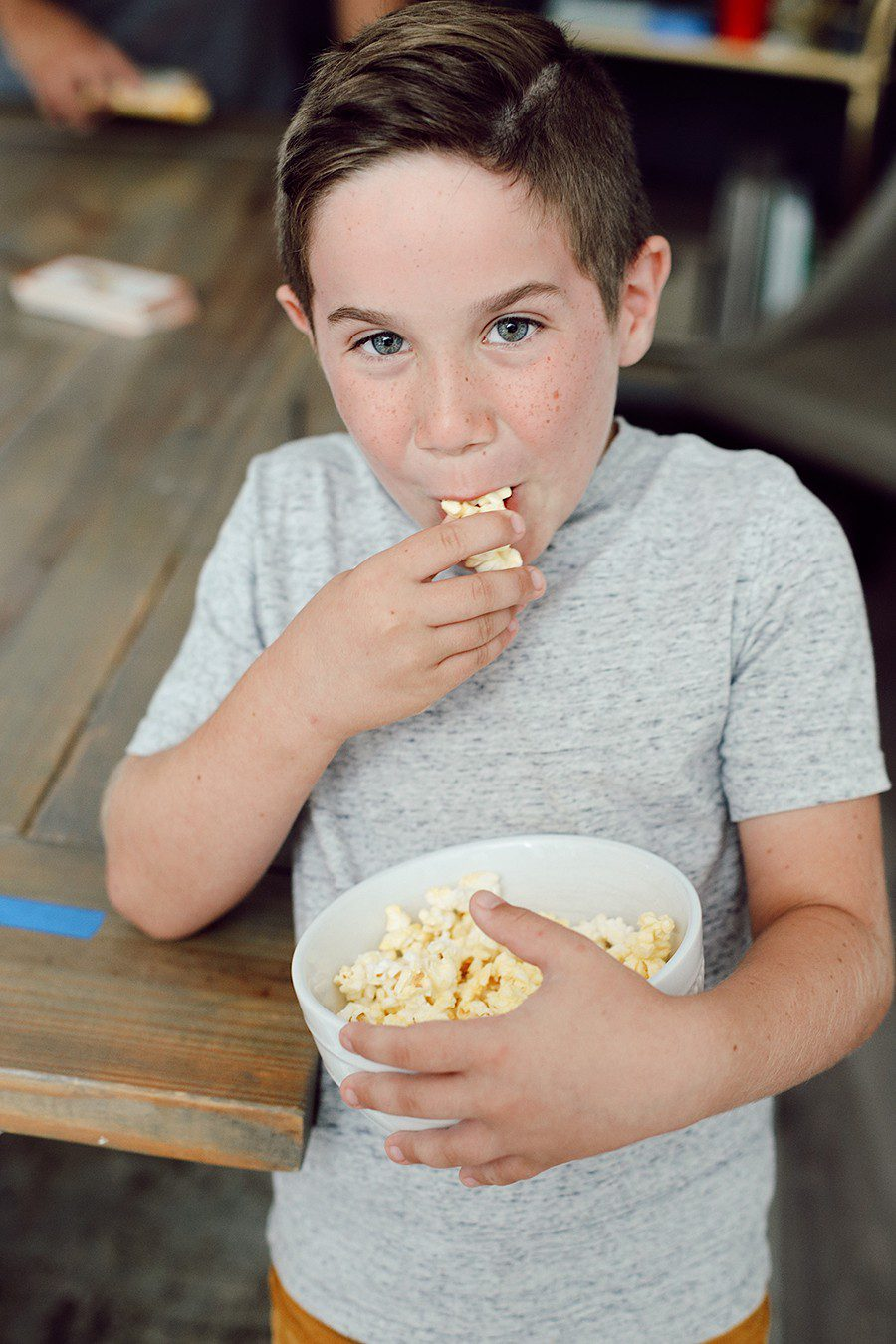 10 Popcorn Games for a Great Family Fun Night | Family Fun Night by popular Florida lifestyle blog, Fresh Mommy Blog: image of a young boy holding and eating out of a bowl of popcorn.