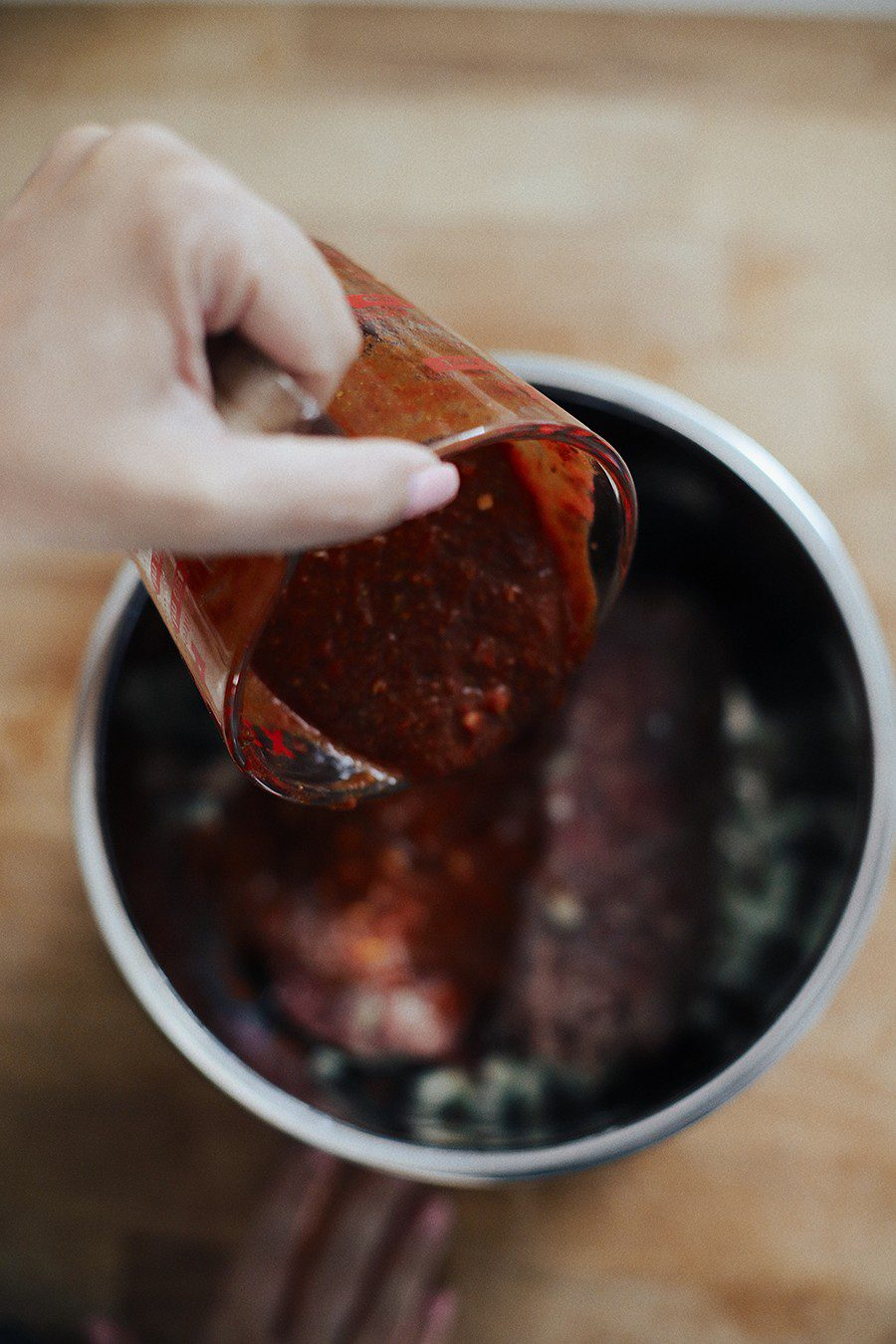 Easy Weeknight Crockpot Meals: Slow Cooker Barbacoa Beef Tacos | Omaha Steaks by popular Florida lifestyle blog, Fresh Mommy Blog: image of a woman pouring a marinade on some raw beef in a slow cooker.