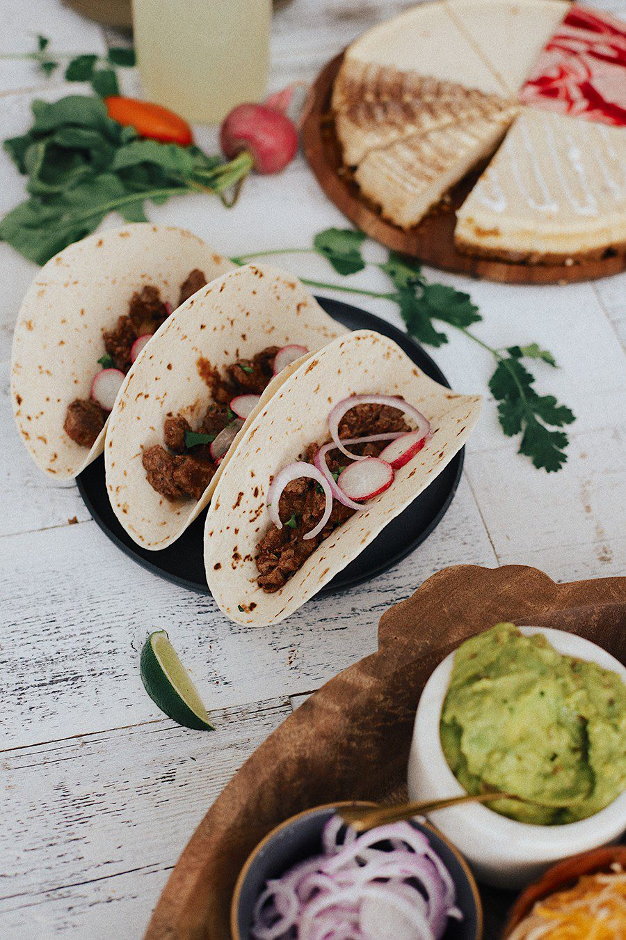 Easy Weeknight Crockpot Meals: Slow Cooker Barbacoa Beef Tacos | Omaha Steaks by popular Florida lifestyle blog, Fresh Mommy Blog: image of barbacoa beef tacos, sliced cheesecake, guacamole, red onions, grated cheese, hard taco shells, sour cream, black olives, and tortillas.