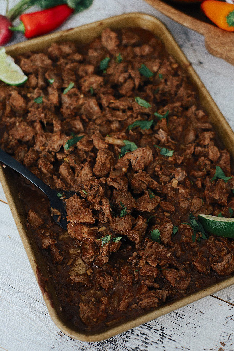 Easy Weeknight Crockpot Meals: Slow Cooker Barbacoa Beef Tacos | Omaha Steaks by popular Florida lifestyle blog, Fresh Mommy Blog: image of barbacoa beef on a cooking tray.