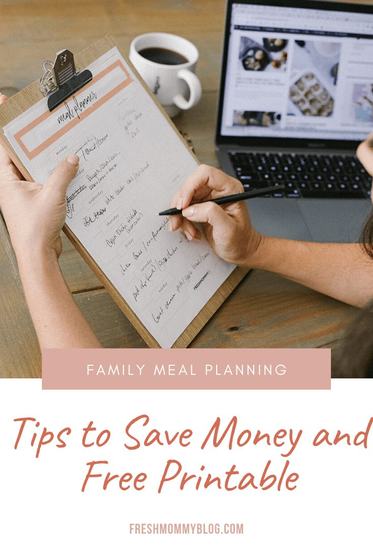 Family Meal Planning Tips to Save Money and Free Printable | Family Meal Planning by popular Florida lifestyle blog, Fresh Mommy Blog: Pinterest image of a woman looking at a meal planner chart on a clipboard while sitting at a table containing a cup of coffee, glasses, a succulent plant and an open Mac laptop.