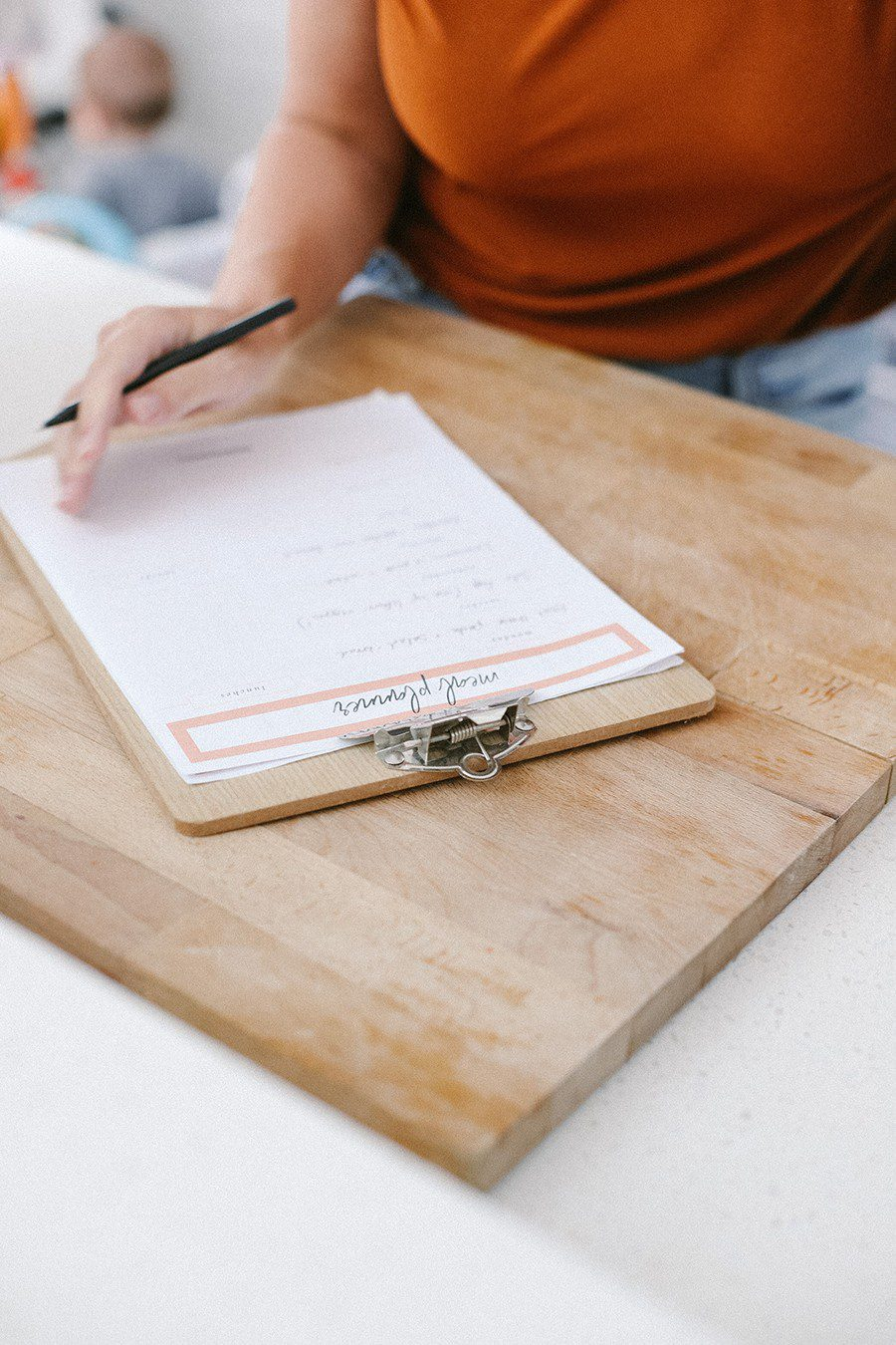 Family Meal Planning Tips to Save Money and Free Printable | Family Meal Planning by popular Florida lifestyle blog, Fresh Mommy Blog: image of a woman looking a meal planning sheet on a clipboard.