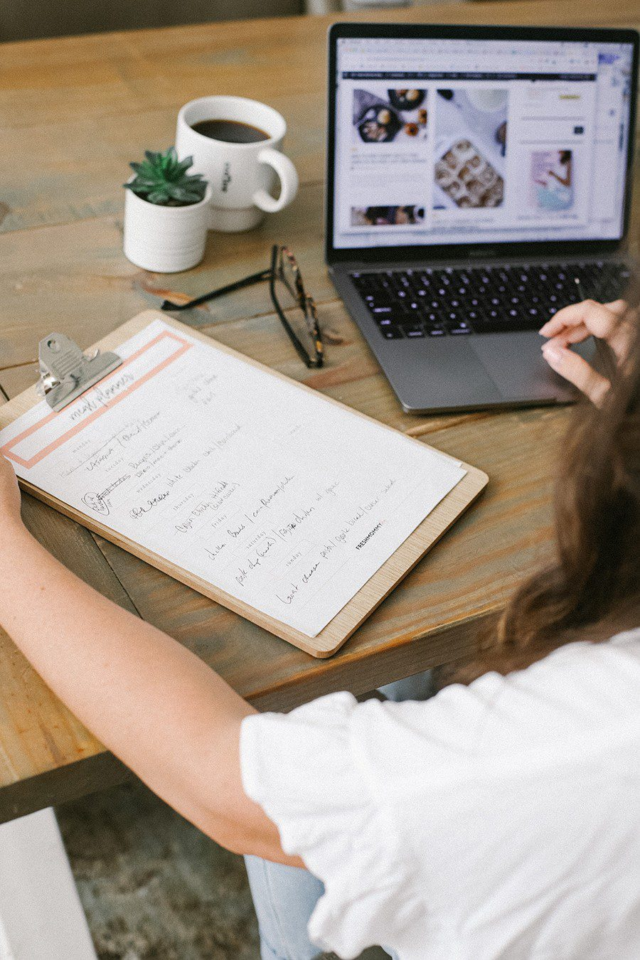 Family Meal Planning Tips to Save Money and Free Printable | Family Meal Planning by popular Florida lifestyle blog, Fresh Mommy Blog: image of a woman looking at a meal planner chart on a clipboard while sitting at a table containing a cup of coffee, glasses, a succulent plant and an open Mac laptop.