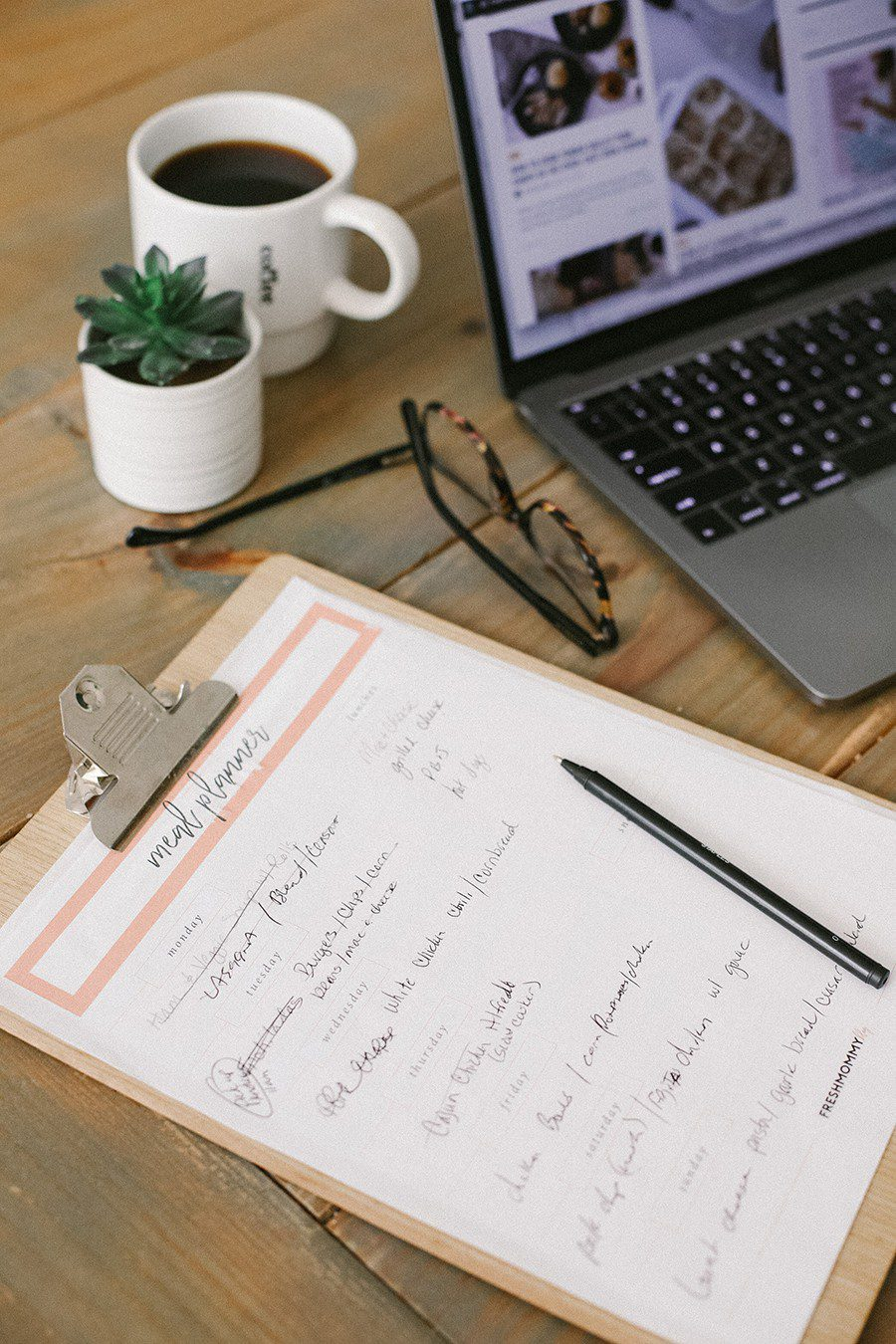 Family Meal Planning Tips to Save Money and Free Printable | Family Meal Planning by popular Florida lifestyle blog, Fresh Mommy Blog: image of a clipboard, cup of coffee, glasses, a succulent plant and an open Mac laptop.