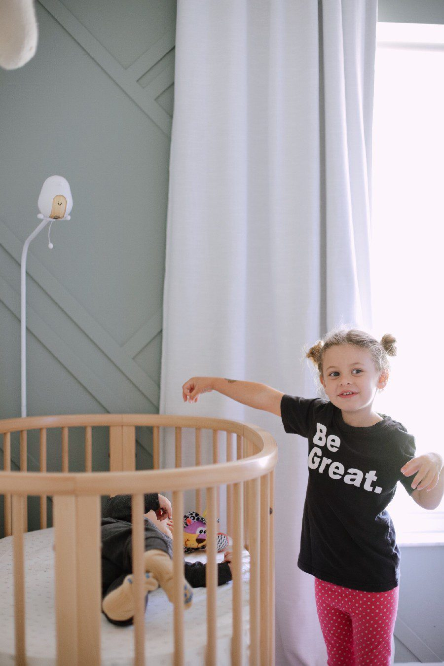 Big sister playing with baby in the stokke sleepi crib. The Best Baby Monitor for Twins - Cubo Ai Smart Baby Monitor Review | Best Baby Monitor by popular Florida motherhood blog, Fresh Mommy Blog: image of a little girl standing next to a baby laying in a stokke sleepi crib.