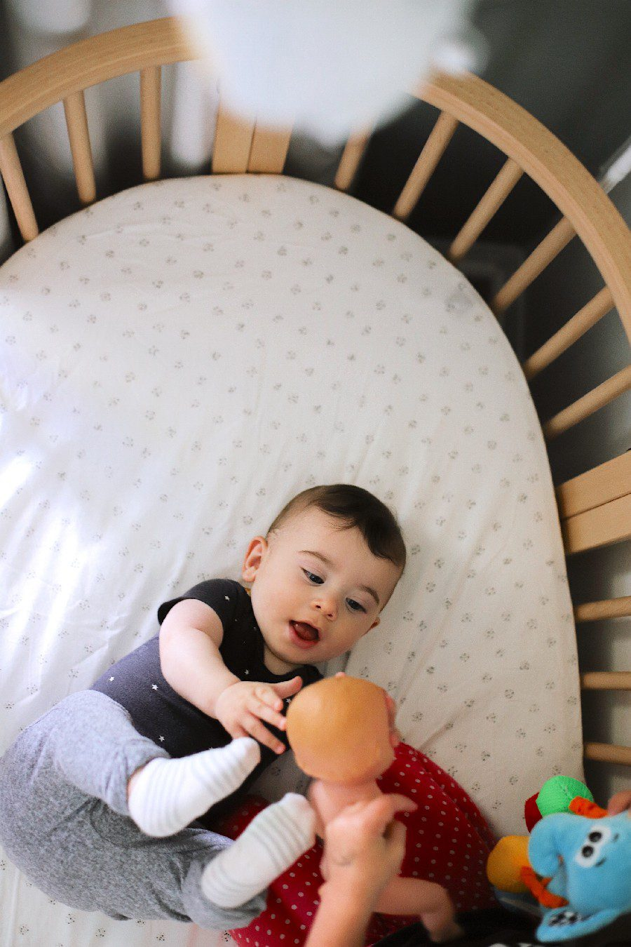 baby in stokke sleepi crib | Best Baby Monitor by popular Florida motherhood blog, Fresh Mommy Blog: image of a young boy standing next to a baby laying in a stokke sleepi crib.