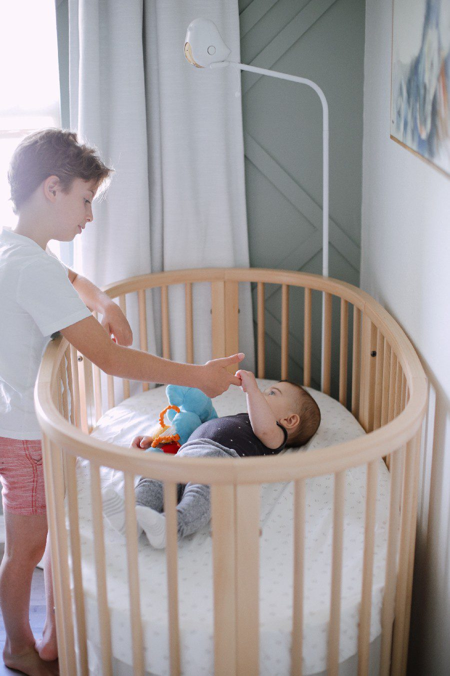 Big brother playing with baby in the stokke sleepi crib. The Best Baby Monitor for Twins - Cubo Ai Smart Baby Monitor Review | Best Baby Monitor by popular Florida motherhood blog, Fresh Mommy Blog: image of a young boy standing next to a baby laying in a stokke sleepi crib.