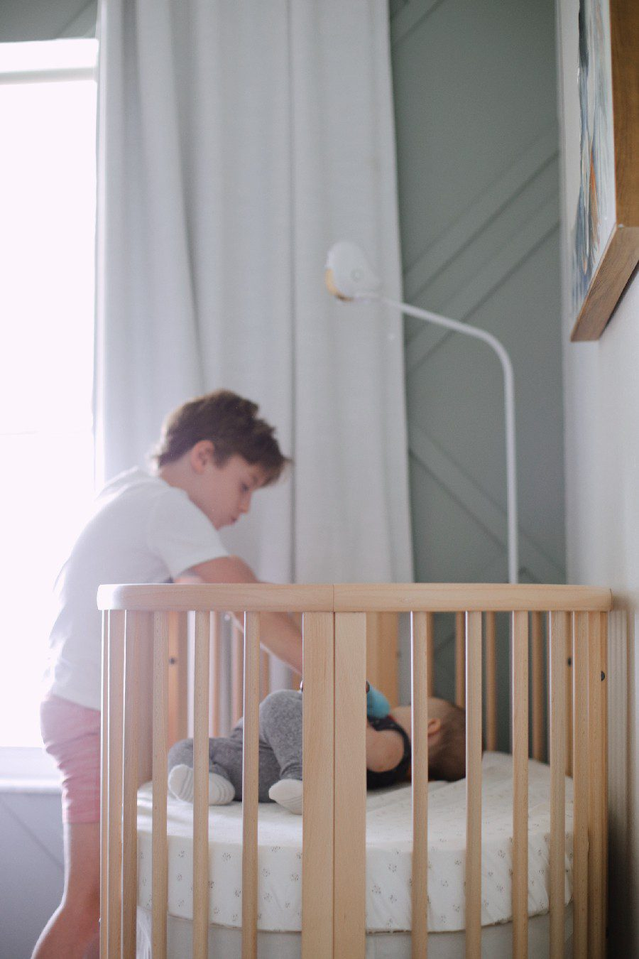 Big brother playing with baby in the stokke sleepi crib. The Best Baby Monitor for Twins - Cubo Ai Smart Baby Monitor Review   Best Baby Monitor by popular Florida motherhood blog, Fresh Mommy Blog: image of a young boy standing next to a baby laying in a stokke sleepi crib.