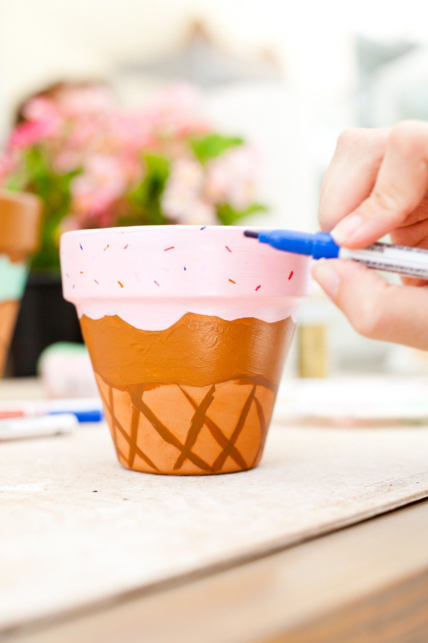 These fun Waffle Cone Ice Cream Painted Flower Pots are a simple to make and even topped with a cherry! Perfect for summer decor, an ice cream social or to satisfy your DIY sweet tooth by popular Florida lifestyle blogger Tabitha Blue of Fresh Mommy Blog.