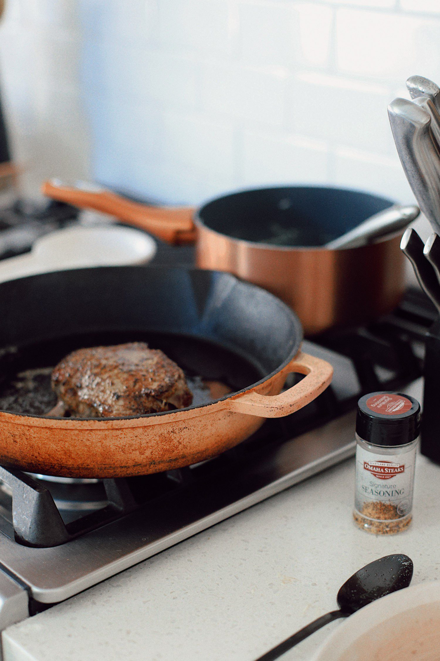 Pan-Seared Steak with Gorgonzola Sauce | Pan Seared Ribeye Steak by popular Florida lifestyle blog, Fresh Mommy Blog: image of ribeye steak cooking in a pan on a gas range stove.