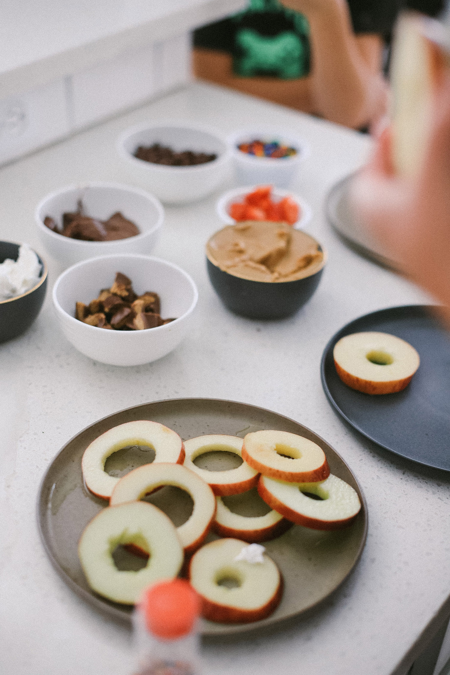 Easy snack ideas for a healthy sweet snacktivity for kids! Apple Donut fun recipe for kids from top Florida blogger Tabitha Blue of Fresh Mommy Blog | Apple Donuts by popular Florida motherhood blog, Fresh Mommy Blog: image of apple slices on a plate next to bowls filled with various toppings.