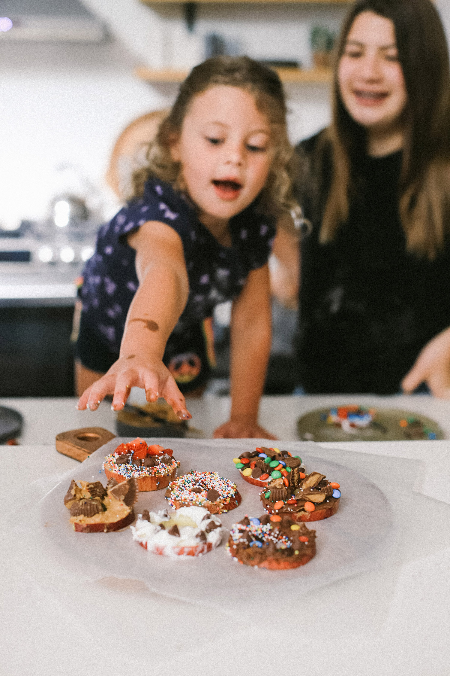 Easy snack ideas for a healthy sweet snacktivity for kids! Apple Donut fun recipe for kids from top Florida blogger Tabitha Blue of Fresh Mommy Blog | Apple Donuts by popular Florida motherhood blog, Fresh Mommy Blog: image of a young girl reaching for a plate of apple slices topped with various toppings like peanut butter, peanut butter cups, sprinkles, chocolate chips, and marshmallow fluff.