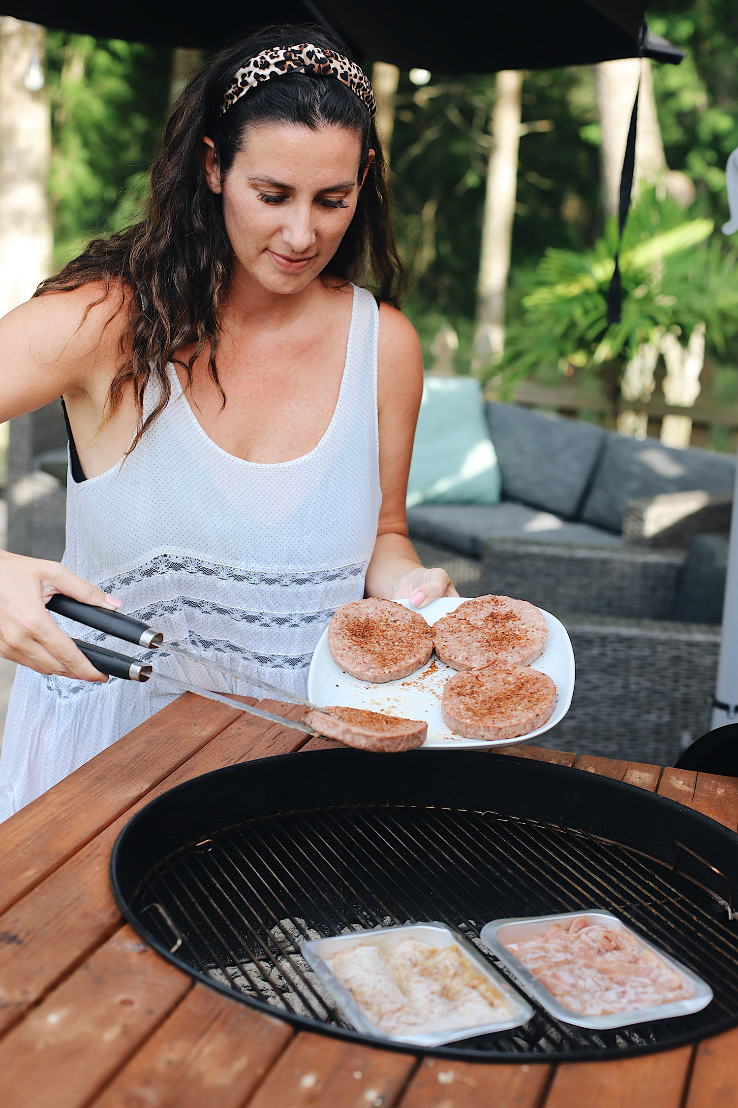 BBQ Bacon Blue Burger for a Tasty Backyard Barbecue. Not your average burger! Juicy beef burgers seasoned with a the perfect amount of spice, topped with smoked bacon jam, sweet bourbon onions, arugula, blue cheese, onion rings, BBQ sauce and a buttery grilled bun! | BBQ Burger by popular Florida lifestyle blog, Fresh Mommy Blog: image of Tabitha Blue grilling some hamburger patties.