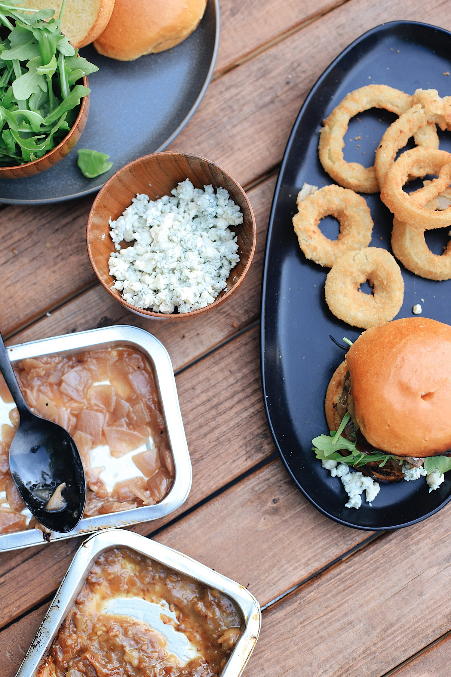 BBQ Bacon Blue Burger for a Tasty Backyard Barbecue. Not your average burger! Juicy beef burgers seasoned with a the perfect amount of spice, topped with smoked bacon jam, sweet bourbon onions, arugula, blue cheese, onion rings, BBQ sauce and a buttery grilled bun! | BBQ Burger by popular Florida lifestyle blog, Fresh Mommy Blog: image of a BBQ Burger with bacon and blue cheese, onion rings, grilled onions, and bacon jam.