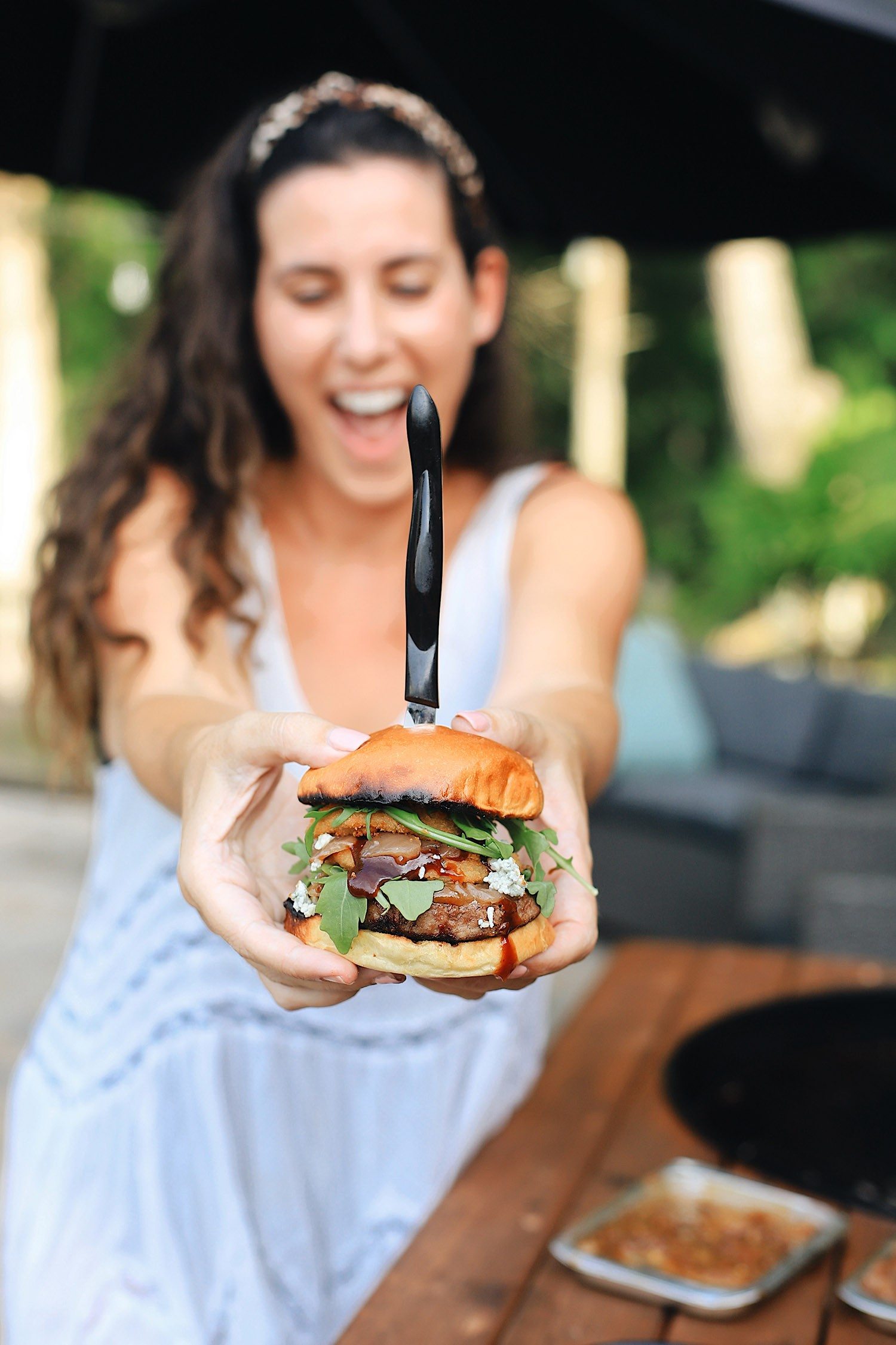 BBQ Bacon Blue Burger for a Tasty Backyard Barbecue. Not your average burger! Juicy beef burgers seasoned with a the perfect amount of spice, topped with smoked bacon jam, sweet bourbon onions, arugula, blue cheese, onion rings, BBQ sauce and a buttery grilled bun! | BBQ Burger by popular Florida lifestyle blog, Fresh Mommy Blog: image of Tabitha Blue holding a BBQ Burger with bacon and blue cheese.