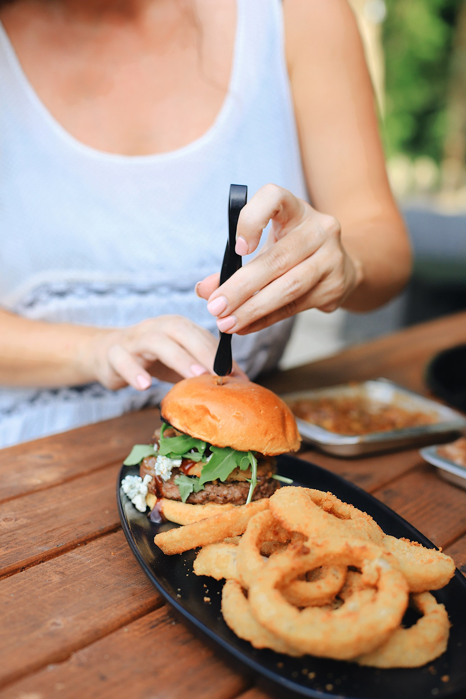 BBQ Bacon Blue Burger for a Tasty Backyard Barbecue. Not your average burger! Juicy beef burgers seasoned with a the perfect amount of spice, topped with smoked bacon jam, sweet bourbon onions, arugula, blue cheese, onion rings, BBQ sauce and a buttery grilled bun! | BBQ Burger by popular Florida lifestyle blog, Fresh Mommy Blog: image of a BBQ Burger with bacon and blue cheese.