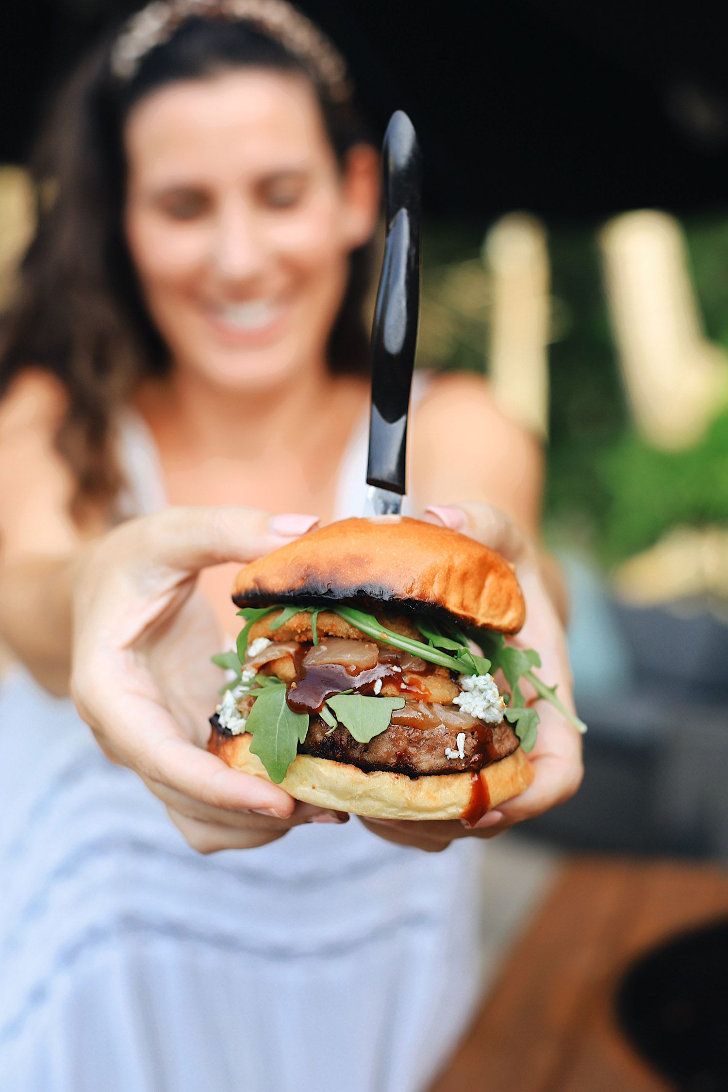 How to Grill Burgers by popular Florida lifestyle blog, Fresh Mommy Blog: image of Tabitha Blue holding a hamburger in between her two hands.