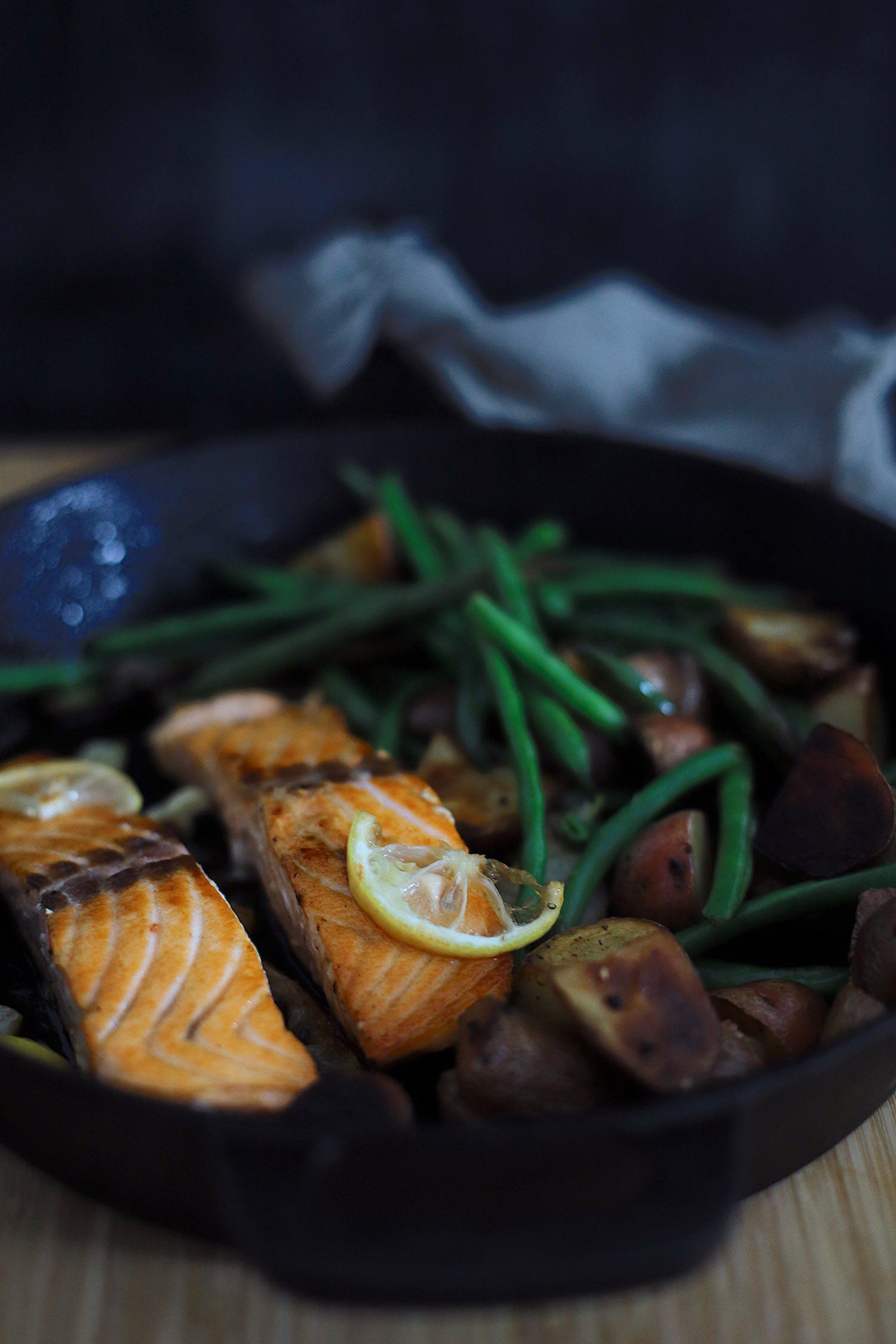 Wondering how to cook salmon? We've got such a simple and easy cast iron skillet salmon recipe with a delicious garlic lemon butter glaze. Pan seared salmon is an easy way to get it just right, every time… in fact, a kid can do it!   Salmon Skillet by possible Florida lifestyle blog, Fresh Mommy Blog: image of salmon, green beans, and potatoes in a skillet.